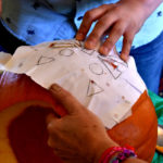 Preschoolers watch a jack-o'-lantern take form in Exeter