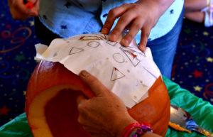 Preschoolers watch a jack-o'-lantern take form in Exeter